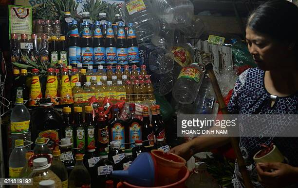 A vendor stands next to her stand selling different type of sauces including fish sauce inside a local market in downtown Hanoi on November 21 2016...