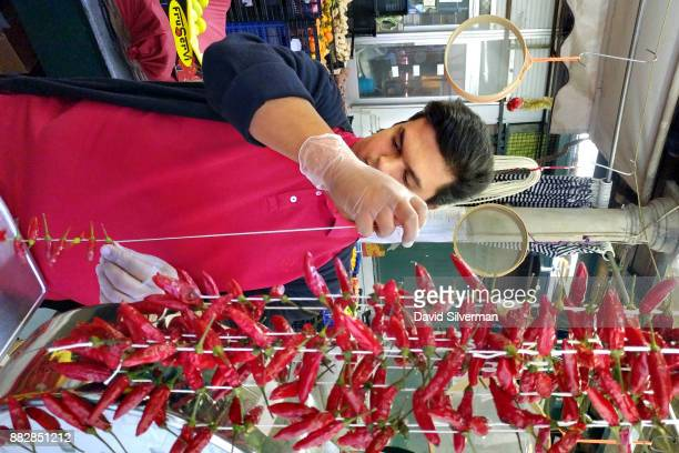 A vendor strings chili peppers for airdrying at a stall in the Bolhão Market on October 6 2016 in the northern Portuguese city of Porto Porto is the...