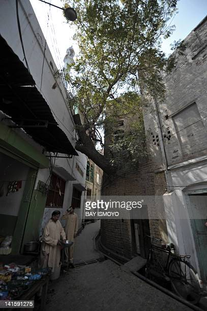 A vendor tends to his stall beside an alleyway in the old town section of Multan on March 17 2012 Multan one of the oldest cities in the Asian...