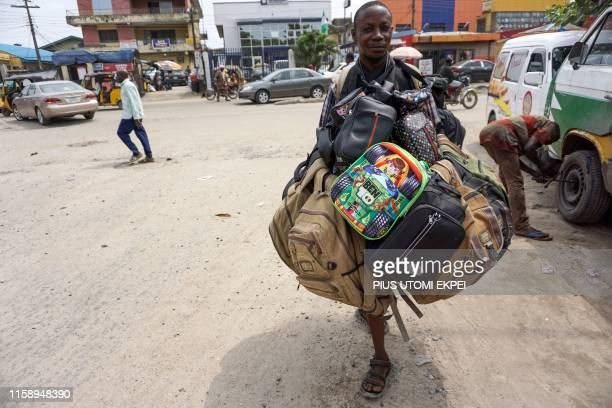 Vendor transports bags of different shapes and sizes in order to attract buyers in the streets of Ladipo's neighbourhood in Lagos, on August 1, 2019....