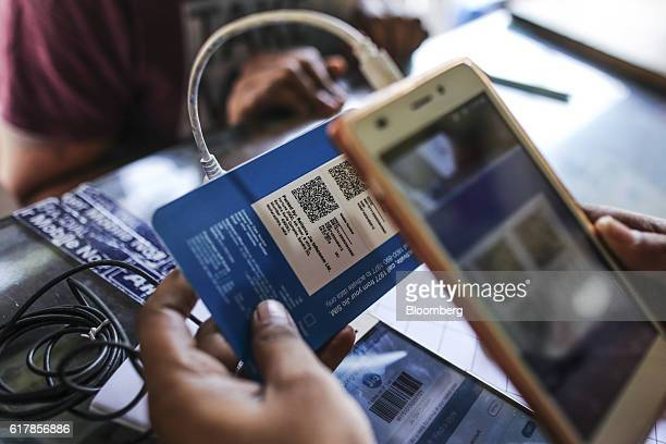A vendor uses a mobile phone to scan a QR code on a SIM card packet for the carrier Reliance Jio the mobile network of Reliance Industries Ltd at a...