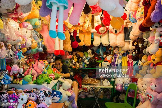 A vendor uses her phone as she minds her stuffed toys stall in a market in Hong Kong on July 6 2016 / AFP / ANTHONY WALLACE
