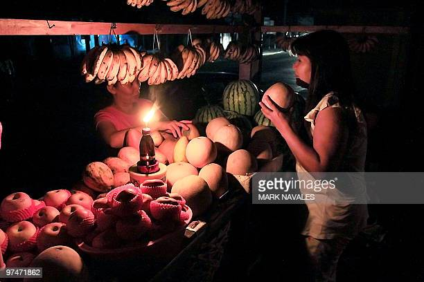 A vendor using a kerosene lamp sell fruit at her booth in the southern Philippine city of Cotabato late on March 5 2010 after the island of Mindanao...