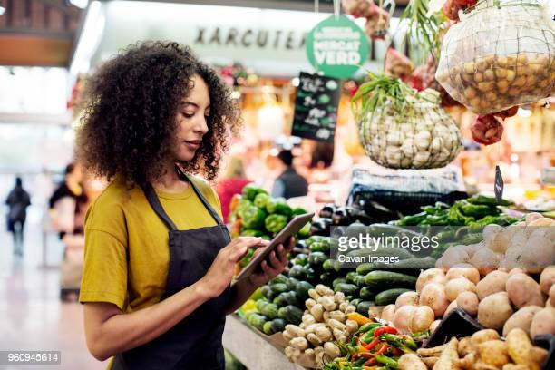 vendor using tablet computer at market stall - market vendor stock pictures, royalty-free photos & images