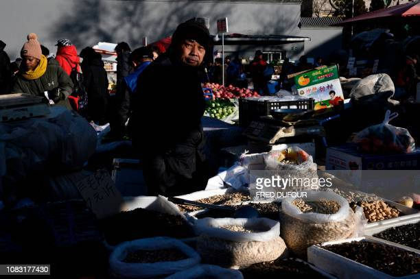 TOPSHOT A vendor waits for clients at a market in the center of Beijing on January 16 2019 China's GDP growth may be significantly slower than...
