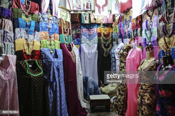 A vendor waits for customers at a clothing stall in Mumbai India on Friday Dec 15 2017 India's inflation surged past the central bank's target...
