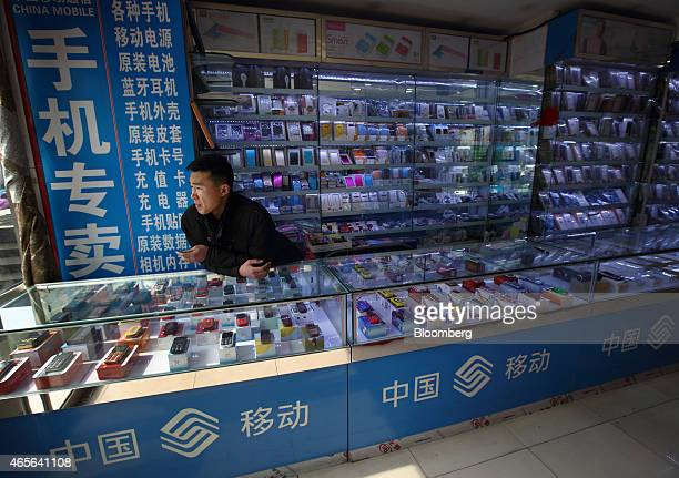 A vendor waits for customers at a mobile phone store in Beijing China on Saturday March 7 2015 China set the lowest economic growth target in more...