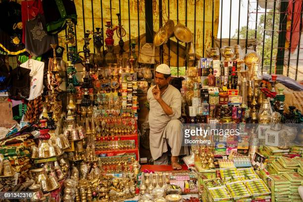 A vendor waits for customers at a stall selling fragrances shisha pipes and metal utensils outside the Jama Masjid during the Muslim holy month of...