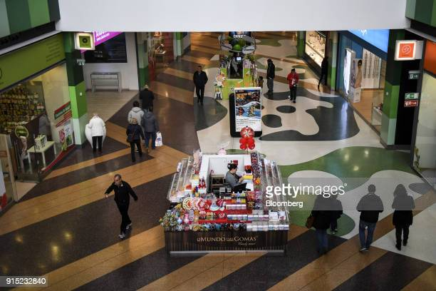 A vendor waits for customers at her candy kiosk in a shopping arcade at the Dolce Vita Tejo shopping mall operated by AXA Real Estate Investment...