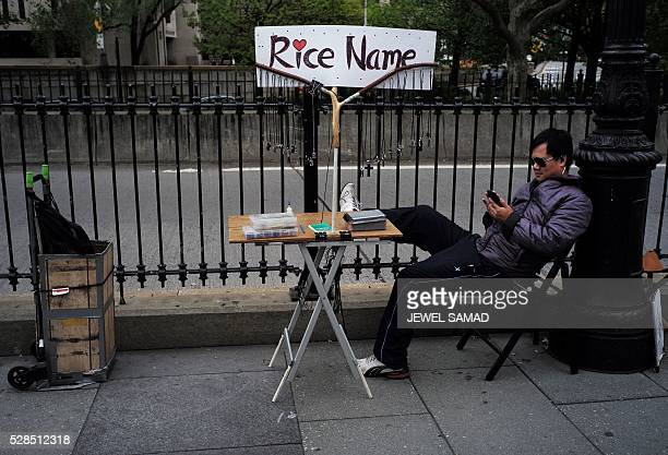 A vendor waits for customers displaying 'Rice Name' necklaces near the Brooklyn Bridge in New York on May 5 2016 / AFP / Jewel SAMAD