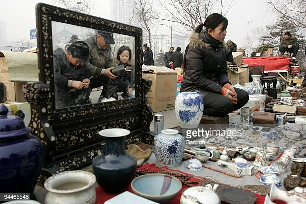 A vendor waits for customers in the openair antique market on Sunday December 13 2009 in Taiyuan in north China's Shanxi province