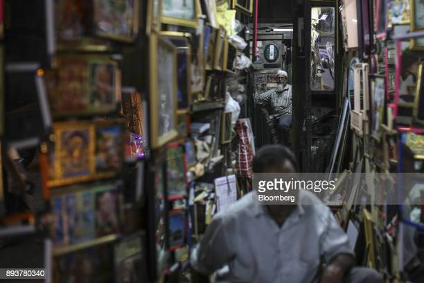 A vendor waits for customers inside a photo frame store in Mumbai India on Friday Dec 15 2017 India's inflation surged past the central bank's target...