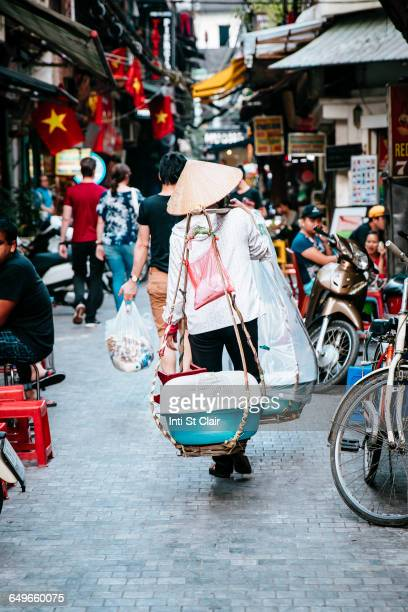 vendor walking on urban street - ho chi minh city stock pictures, royalty-free photos & images