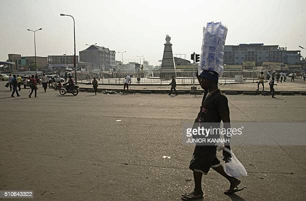 A vendor walks along an empty main road in central Kinshasa on February 162016 after a strike by bus taxi and motorcycle companies was called by a...