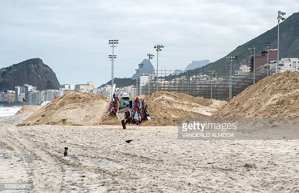 A vendor walks along Copacabana beach next to the construction site of the Olympic beach volleyball stadium for the Rio 2016 Olympic and Paralympic...