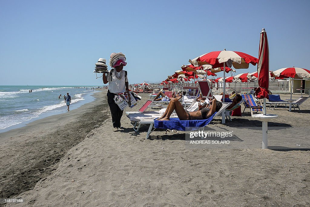 A vendor walks alongside sunbathers on t : News Photo