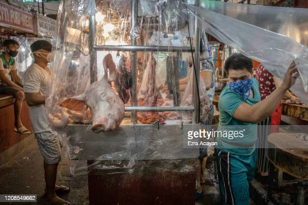 Vendor walks out from his stall covered in plastic to enforce social distancing inside a wet market on March 30, 2020 in Las Pinas, Metro Manila,...
