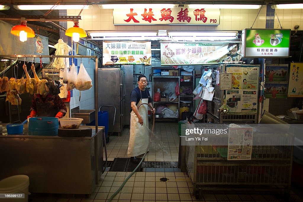 A vendor washes empty chicken cages at the Kowloon City Market on April 12, 2013 in Hong Kong. Local authorities have stepped up the testing of live poultry imports from China to include a rapid test for the H7N9 'bird flu' virus. Measures were put in place as the tenth victim of the influenza strain was confirmed in mainland China yesterday.