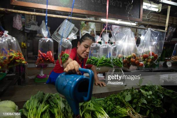 Vendor waters vegetables at a wet market in Patong, Phuket, Thailand, on Sunday, Dec. 20, 2020. The tepid response to Thailands highly publicized...