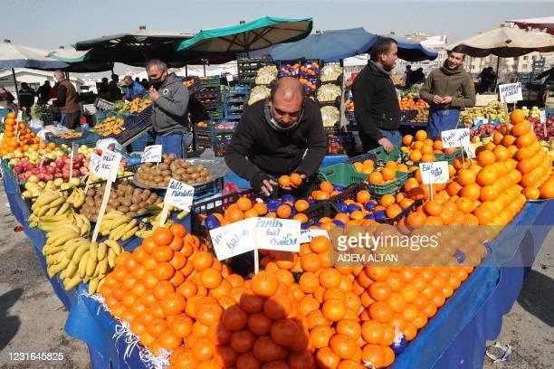 Vendor wearing a protective mask arranges his stall at a local market, amid the coronavirus disease outbreak in Ankara on February 22, 2021. - Ankara...