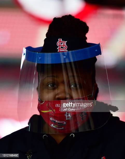 Vendor wears a face mask and a face shield while she help a fan prior to the St. Louis Cardinals home opener against the Milwaukee Brewers at Busch...