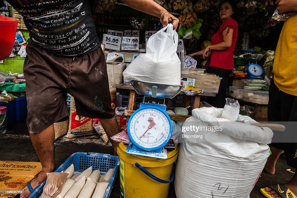 A vendor weighs a bag of rice at a store in Manila, the Philippines, on Tuesday, Jan. 22, 2013. Philippine government bonds advanced on speculation the central bank will hold its benchmark interest rate at a record low at a meeting tomorrow, supporting demand for the nation's debt. Photographer: Julian Abram Wainwright/Bloomberg via Getty Images