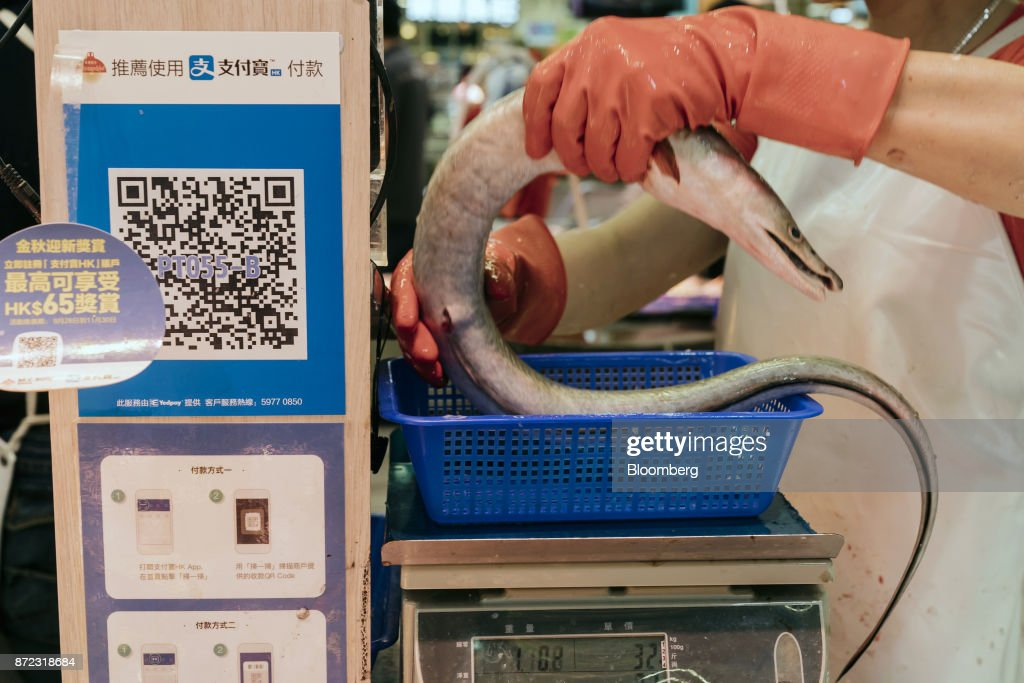 A vendor weighs an eel as a merchant quick response (QR) code and payment instructions for Ant Financial Services Group's Alipay, an affiliate of Alibaba Group Holding Ltd., are displayed at a fish stall inside MC Box Po Tat Market in Hong Kong, China, on Tuesday, Nov. 7, 2017. Ant Financial, which has been valued as high as $75 billion, is the world's most valuable closely held fintech company. Photographer: Anthony Kwan/Bloomberg via Getty Images