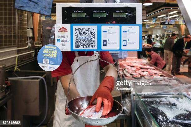 A vendor weights a piece of fish as a merchant quick response code and payment instructions for Ant Financial Services Group's Alipay an affiliate of...