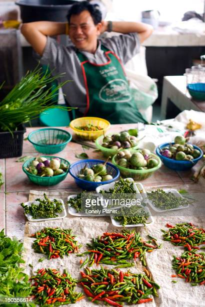 vendor with chillies and peppercorns in foreground at mae nam morning market. - ko samui stock photos and pictures