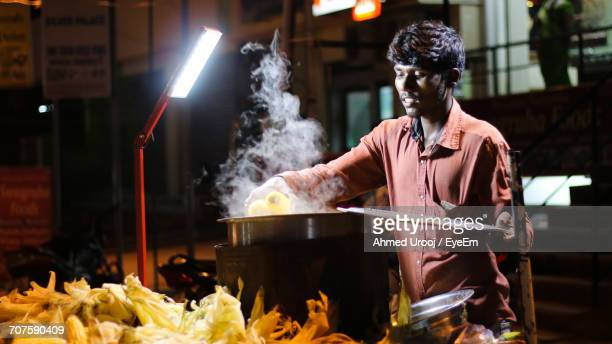 vendor with corns by market stall at night - one night stand stock-fotos und bilder