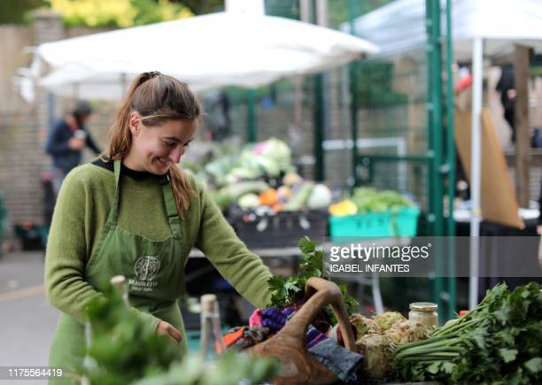 A vendor works at the East Sussex's Brambletye Fruit Farm's food stall at The Spread farmers' market in Primrose Hill north west London on October 5...