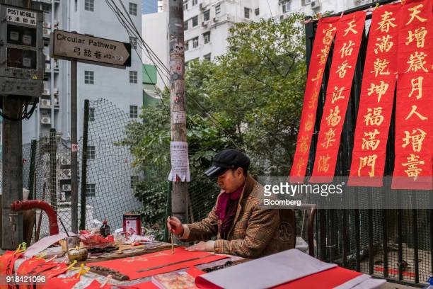 A vendor writes Chinese calligraphy on decorations at a market stall ahead of Lunar New Year in the Sheung Wan district of Hong Kong China on...