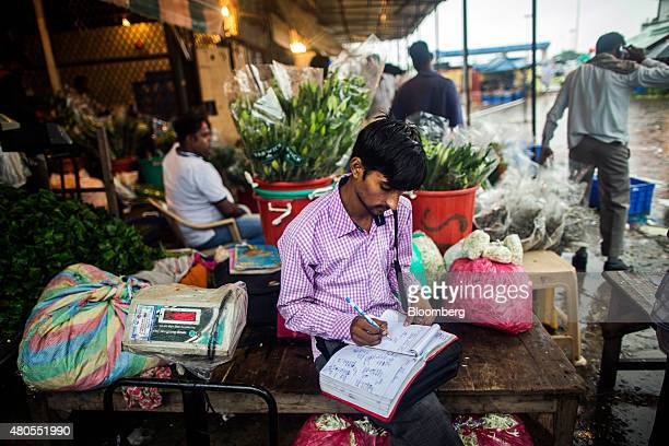 A vendor writes in a notebook at the Ghazipur Wholesale Flower Market in New Delhi India on Sunday July 12 2015 The top forecasters for India's rupee...
