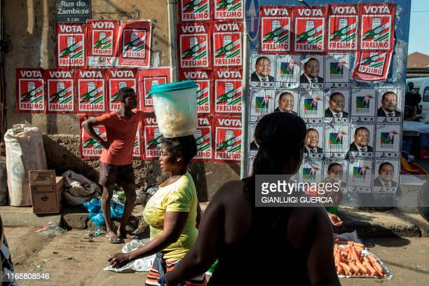 Vendors and clients walk by a wall plastered with Mozambican Presidential Election campaign posters at the Xipamanine market in Maputo, Mozambique,...