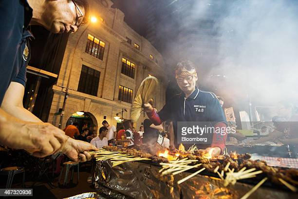 Vendors barbecue satay at the Lau Pa Sat food court as commercial buildings stand illuminated at night in the central business district city of...