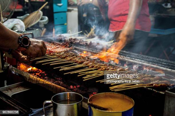 vendors busy grilling satay - singapore - singapore stock pictures, royalty-free photos & images