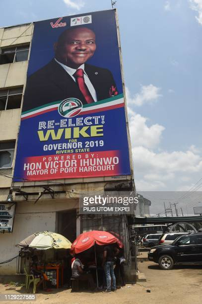 Vendors display their goods at a roadside stall under a campaign billboard of gubernatorial candidate of the Peoples Democratic Party in Rivers State...