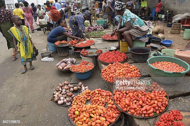 Vendors display tomatoes and pepper at Mile 12 market in Lagos on June 21 2016 Ordinary Nigerians are feeling the full effects of spiralling...