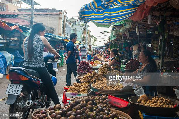 Vendors hawk tropical fruits at an afternoon wet market or fruit and vegetable market at Chao Doc a town on the Bassac River in the Mekong Delta and...