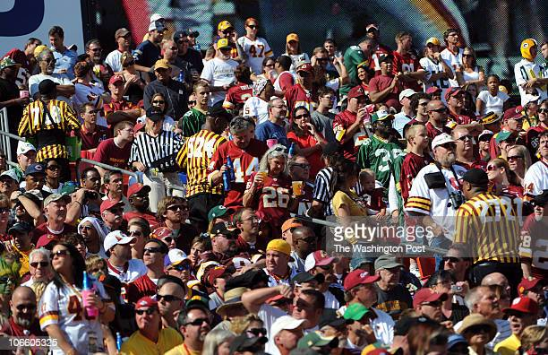 Vendors in striped jerseys bend in with the colorful crowd that packs the stands during the game against the Green Bay Packers at FedEx Field on...