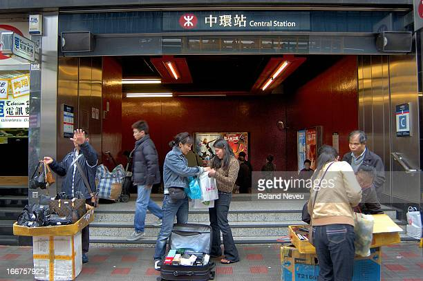 Vendors of counterfeit goods sell their wares at the entrance of a subway station in Hong Kong..