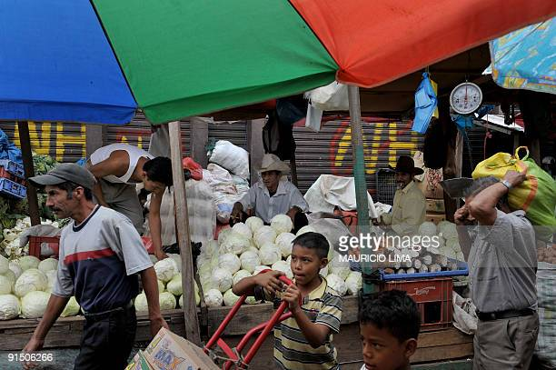 Vendors offer vegetables at the central market in Tegucigalpa Honduras on October 6 2009 Honduran coup leader Roberto Micheletti must give up and...
