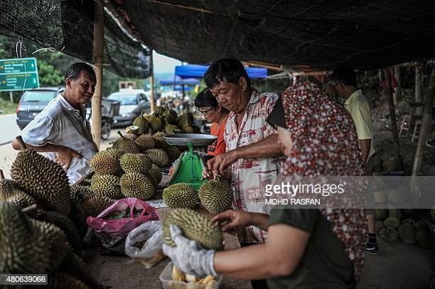 Vendors peel durian fruits for customers at a roadside shop in Karak in the suburbs of Pahang outside Kuala Lumpur on July 14 2015 The durian locally...