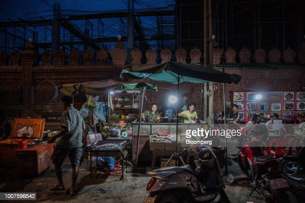 Vendors prepare food at a roadside stall at night in Phnom Penh Cambodia on Sunday July 29 2018 Cambodian Prime MinisterHun Senextended his...