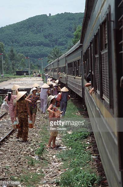 Vendors sell food and drinks to passengers on the famous Reunification Express train which runs from Saigon to Hanoi in Vietnam taking approximately...
