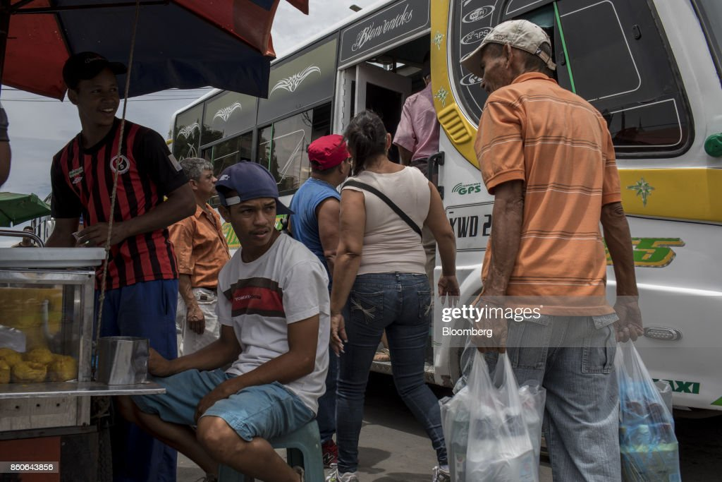 Vendors sell food next to a bus stop near the San Antonio International Border in Cucuta, Colombia, on Thursday, Sept. 21, 2017. For weeks, Venezuelans have been flocking by the busload to San Antonio del Tachira, a border town of some 62,000 residents, fleeing as President Nicolas Maduro consolidates autocratic power. According to Colombia's migration authority, the number of foreigners entering Cucuta, the first major city across the bridge, more than doubled this summer. Photographer: Nicolo Filippo Rosso/Bloomberg via Getty Images