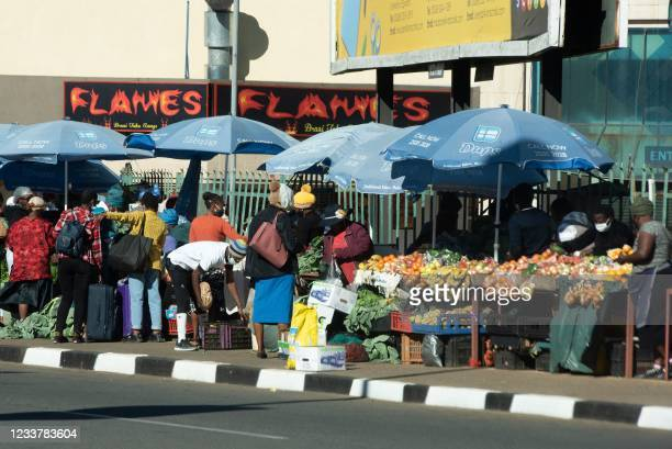 Vendors sell fruit and vegetables on the city streets of Mbabane on July 3, 2021 as a tense calm returns to Eswatini after days of violent widespread...