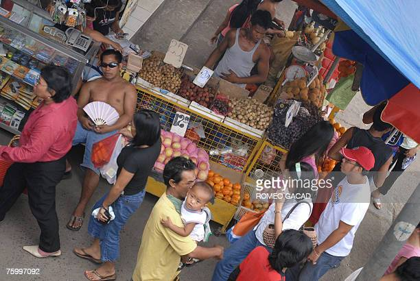Vendors sell fruit mobile phones and accesories on a sidewalk store in Manila 23 July 2007 Philippine consumer prices rose at a higher than expected...