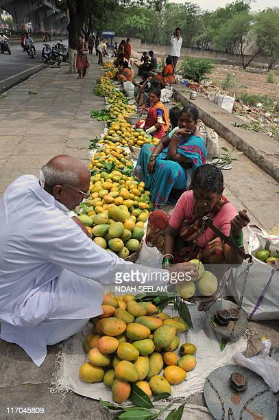 Vendors sell mangoes by a sidewalk in Hyderabad on June 20 2011 India's population is estimated at more than 11 billion and is growing at 155% a year...