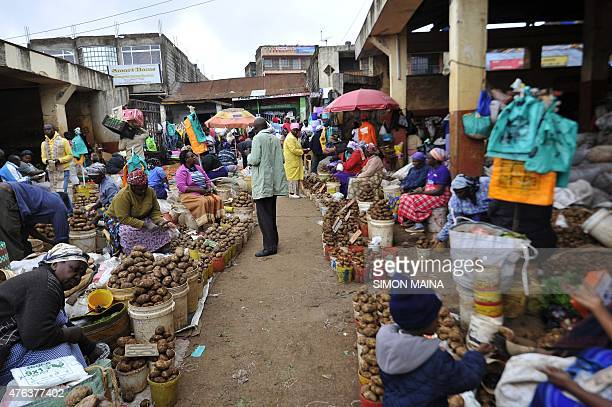 Vendors sell potatoes in a street market in Kabete on the outskirts of Nairobi on June 8 2015 The city knows a recent increase of large shopping...
